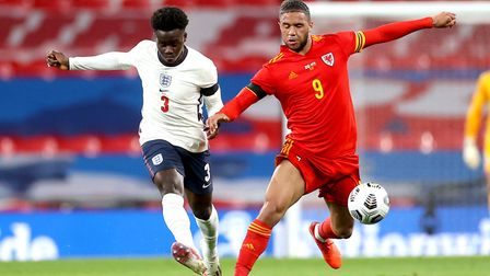 England's Bukayo Saka (left) and Wales' Tyler Roberts battle for the ball during the international f