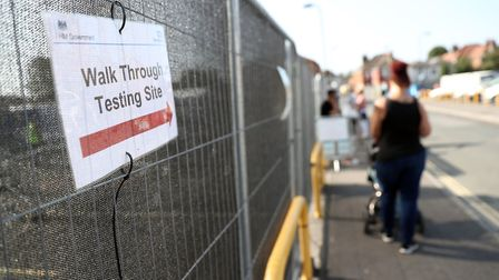 People queue up outside a walk through coronavirus testing centre. Picture: Andrew Matthews/PA Wire