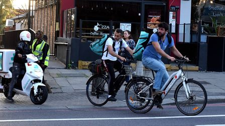 Cyclists and e-scooter leave the Deliveroo site in Swiss Cottage. Picture: Polly Hancock