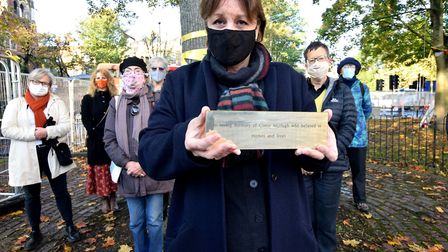 Widow Brenda McHugh holds a plaque dedicated to her late husband Conor, surrounded by fellow campaig