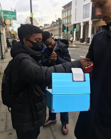 Hackney New School Students sell poppies outside their school gate for remembrance day. Picture: Hac