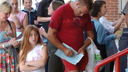 Parents and guardians fill in forms for their children as they queue for auditions for kids Stars in