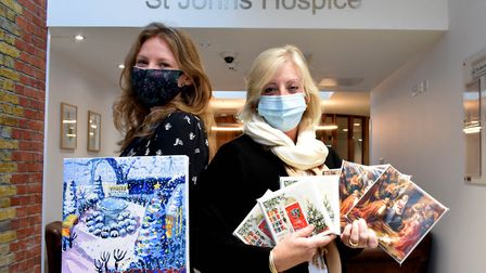 Staff members Sophie Gray and Carol Clifford with St John's Hospice Christmas cards and a painting o