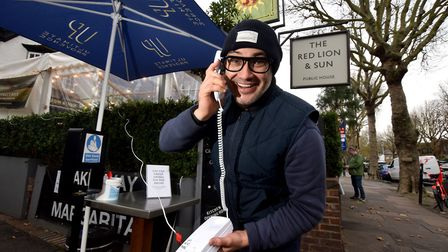 Heath Ball, landlord of The Red Lion & Sun in Highgate, tries out his new order by phone system outside the pub which...