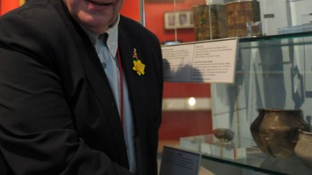 Peter Stewart, Director of Romford Museum Collection, stands in front of a cabinet containing roman Artifacts such as a...