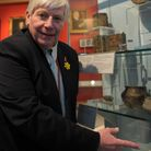 Peter Stewart, Director of Romford Museum Collection, stands in front of a cabinet containing roman Artifacts such as a hand ...