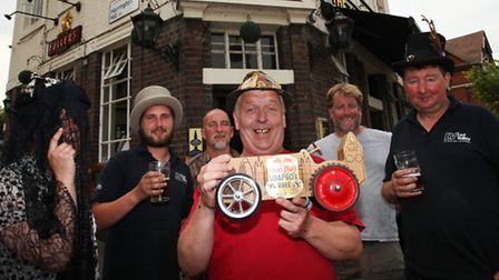 Anchor & Hope Pub owner Russell Winn, centre, holds the Red Bull Soapbox Race 2013 trophy after the Coffin Dodgers team...