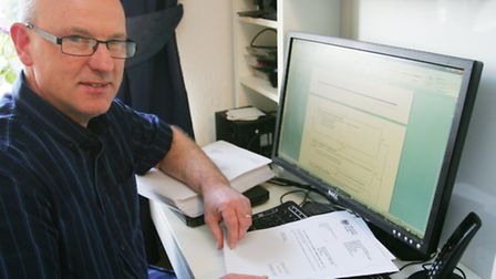 Peter Baker scrolling through reams of information on the bedroom tax
