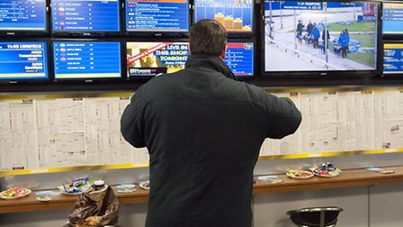 A punter makes his bets at a William Hill shop