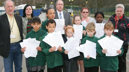 Headteacher Adrian McNeillis and pupils hold leaflets urging road users to slow down outside Brookside Junior School.