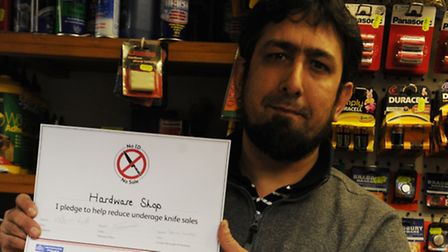 Shop manager Waseem Butt holds his pledge which ensures that knives are kept behind the counter and are sold responsibly