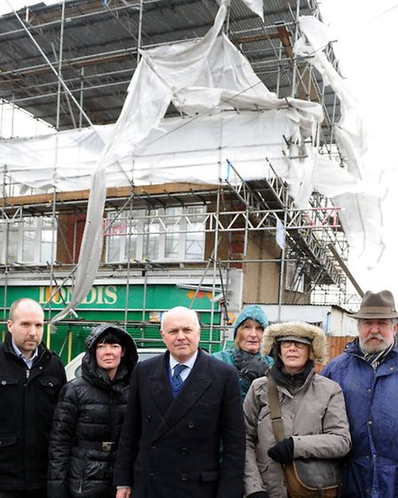 Iain Duncan Smith with a group of local residents in front of a Londis shop that was destroyed in a fire.