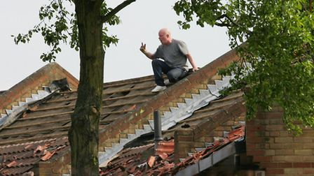 Angry resident on the roof of his house in Forest Gate