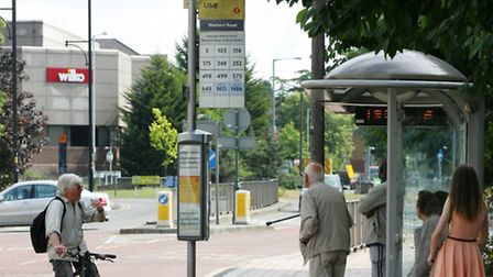 A cyclist tells commuters that the bus stop is not in use and that buses are not stopping there