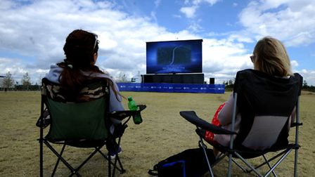 Members of the public watch the Tour de France on a huge screen in Queen Elizabeth Park.