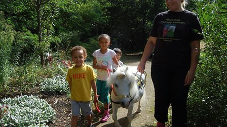 Youngsters taking the unicorn around the Richard House gardens