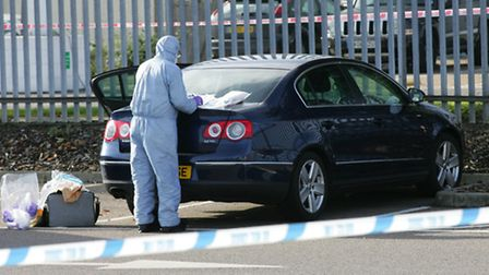 Forensic experts examine the car for evidence