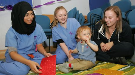 Student midwife Humaairah Jama, midwife Phoebe Langer and mum Leanne Ryder with Karl Armsterong, age one