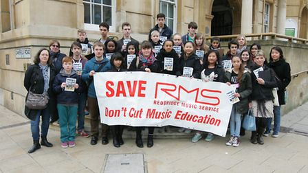 Music school students collecting signatures for petition against cuts in Ilford Town.