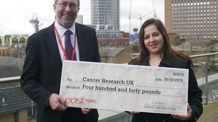 John Grimmer from East Thames Group presents Ruch Sharma from Cancer Research UK with a cheque for £440.