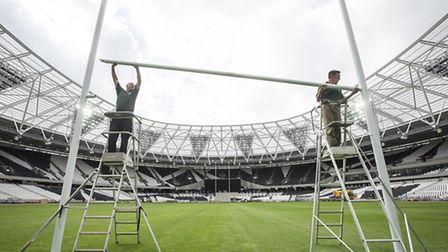 Peter Spence and Steve Heap install the crossbar for the rugby posts at the former Olympic Stadium in preparation for the...
