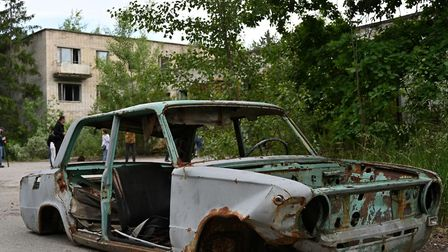 A picture taken on June 7, 2019, shows the wreckage of a car in the ghost city of Pripyat in the Che
