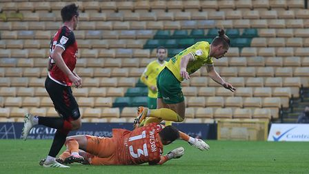 Przemyslaw Placheta of Norwich City tumbles under a challenge from Ben Wilson of Coventry City to earn a penalty in...