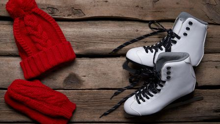 Winter activities. Pair of White Ice Skates and knit hat on weathered wooden planks, top view