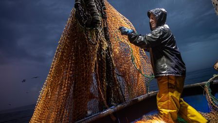 Skipper Stuart Hamilton, pulls in the nets while fishing for flatfishin the English Channel from a Hastings fishing boat...