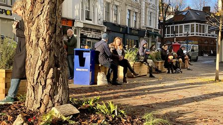 People sitting on the CIL-funded planters at Belsize Village. Picture: Linda Grove.