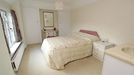a double bedroom with central double bed, bedside cabinet, white window and radiator under, beige carpet and walls and a...