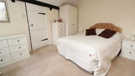 bedroom with double bed and beige headboard, beige carpet and walls, white stable-door and white furniture
