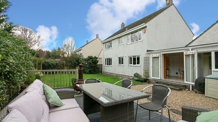 back of house with extension and lawned garden with raised deck and luxurious garden furniture