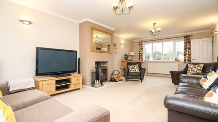 beige large living room with window at far end, wood-burner and furniture