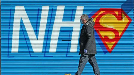 A man walks past a sign created in support of the NHS during the pandemic