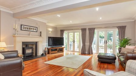 The sitting room has a feature log burner and two sets of patio doors, leading to the rear garden. Picture: Cassidy & Tate