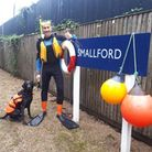 Nast Hyde Halt Mike, pictured here with his four-legged friend Baz, helped passers by across the flood water on Sunday.