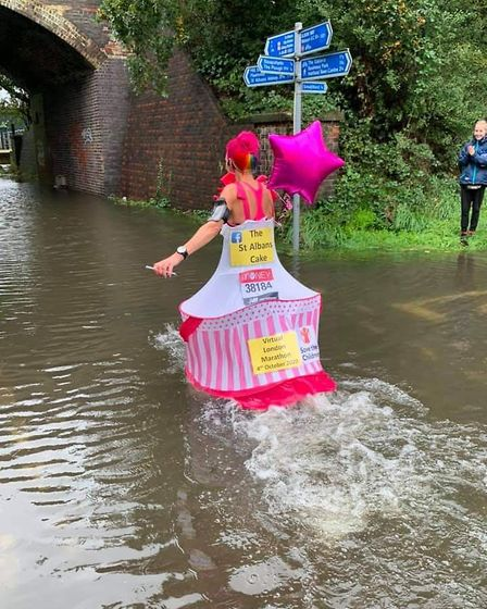 Soggy bottom: Flood water didn't stop Anna Bassil, 41, from running 26.2 miles for Save the Children on Sunday. Picture...