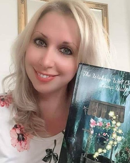 Liana Wall holding children's book Believe and You Shall Find, the first book in her The Wishing Well Collection.