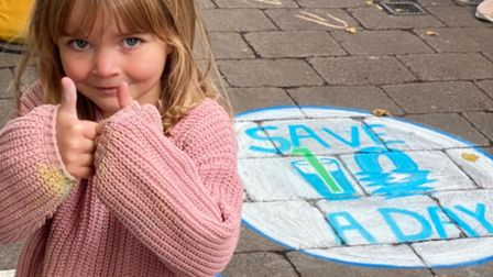Karen Snook's daughter with one of the chalk sketches encouraging St Albans residents to save 10 litres of water a day.