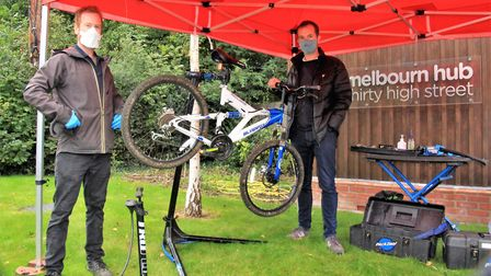 Mechanic David Whateley hands over a repaired bike to customer Daniel King at Melbourn Community Hub. Picture: Clive Porter