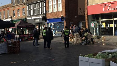 Police order a flower seller to remove their wares from St Albans Charter Market on Saturday.