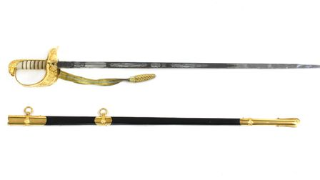 Wing Commander?s Ratcliff?s dress sword, scabbard and ribbon with a gilt brass guard bearing the RAF insignia has a guide...