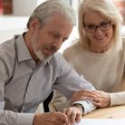 Happy older family couple husband and wife sign legal paper insurance contract write will testament,