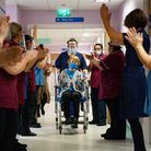 Margaret Keenan, 90, is applauded by staff as she returns to her ward after becoming the first perso