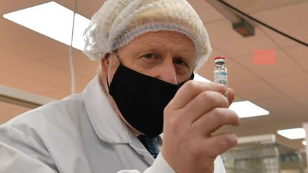 Prime Minister Boris Johnson (left) holds a vial at the 'fill and finish' stage of the manufacturing process of Covid-19...