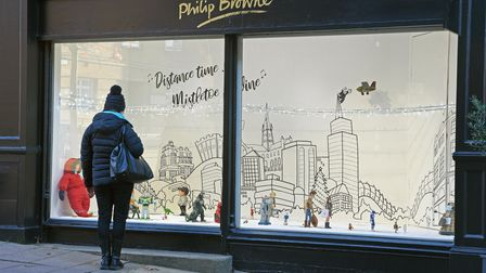 A member of the public admiring the festive window display at Philip Browne Menswear on Guildhall Hi