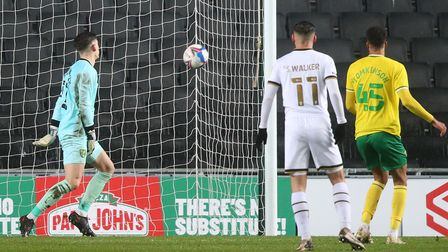 Jon McCracken of Norwich City can't stop Kieran Agard of Milton Keynes Dons scoring his sides 1st go