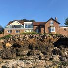 big detached house built on rocky beach