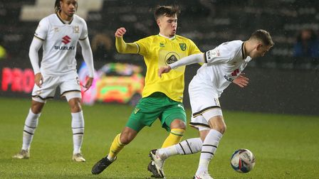 Josh Giurgi of Norwich City and John Freeman of Milton Keynes Dons in action during the Papa Johns T